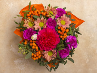 A beautiful bouquet of flowers with a rowanberry. View from above. On a textured, light background